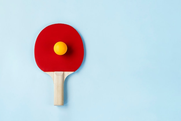 Czerwona rakietka do ping-ponga i piłka na jasnoniebieskim tle