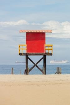 Czerwona ratownik poczta na copacabana plaży z morzem i niebieskim niebem w rio de janeiro.