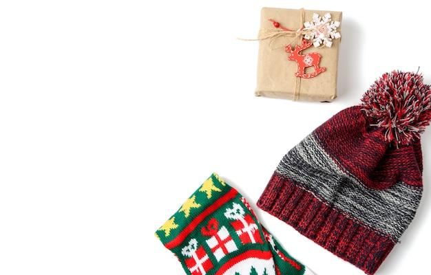 Czerwona ręka i pudełko zawinięte w brązowy papier pakowy i związane liną, prezent na białym tle, widok z góry