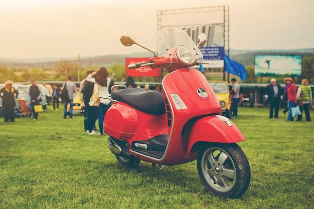 Czerwona retro hulajnoga na trawie