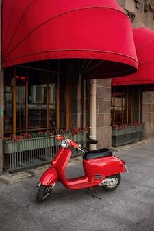 Czerwona rocznik hulajnoga parkująca na chodniczku pusta miasto ulica.