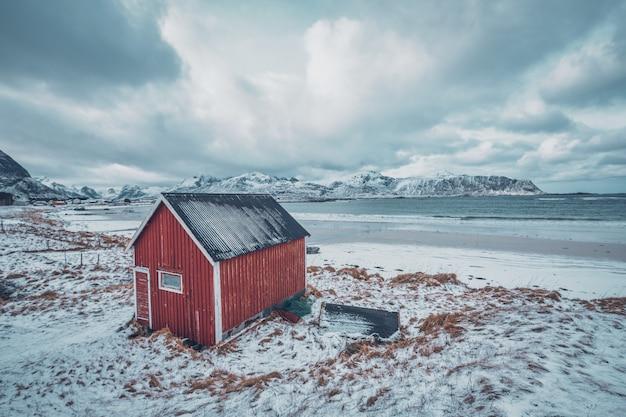 Czerwona rorbu domu jata na plaży fjord, norwegia