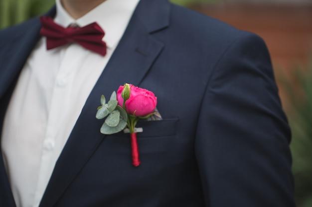 Czerwona róża boutonniere na garniturze pana młodego