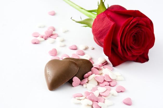 Czerwona róża, czekoladowy bonbon w kształcie serca i cukierki