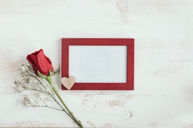 Czerwona róża i biały kwiat z sercem i ramą