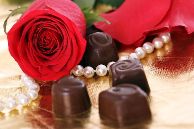 Czerwona róża i cukierki czekoladowe