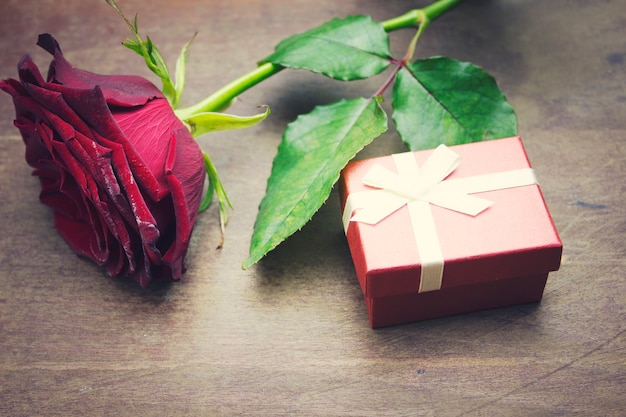 Czerwona róża i pudełko na drewnianym stole