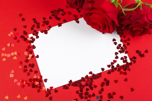 Czerwona róża i pusta karta upominkowa dla tekstu