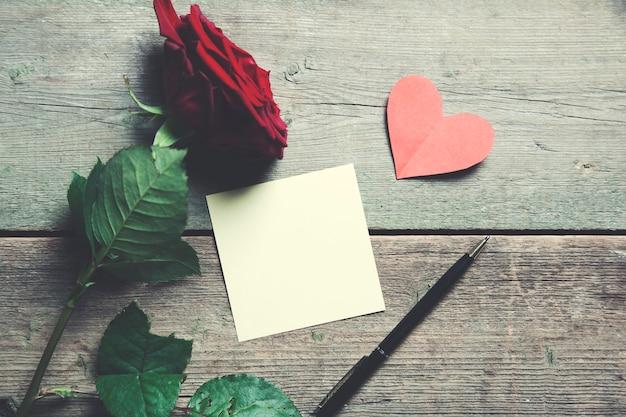 Czerwona róża, papierowe serce i papierowa notatka