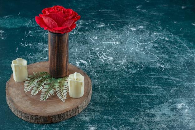 Czerwona róża w drewnianym dzbanku obok świecy na desce, na białym tle.
