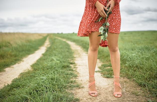 Czerwoną różę trzyma w obu rękach dziewczyna w sukience i sandałach na stopach