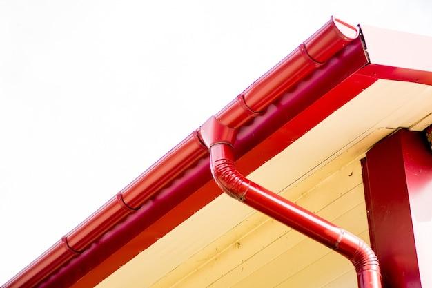 Czerwona rynna na dachu domu.