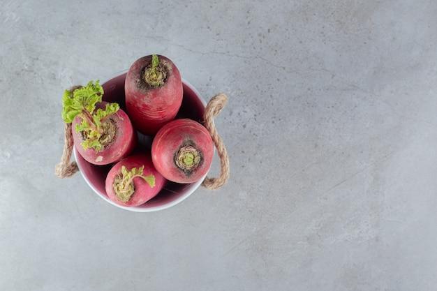 Czerwona rzodkiew i liście na szarym tle. zdjęcie wysokiej jakości