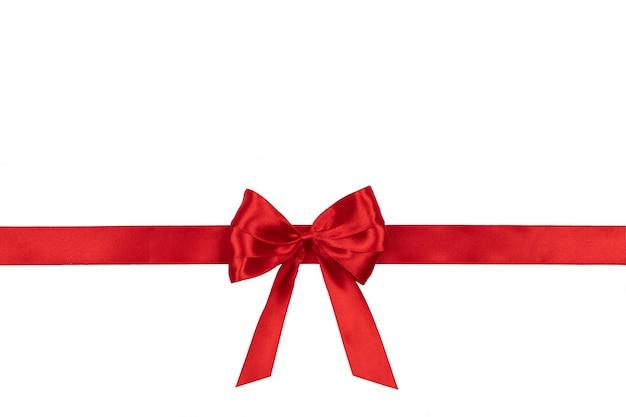 Czerwona satynowa kokardka wiązana na białym tle z miejscem na tekst