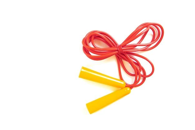 Czerwona skakanka z żółtymi uchwytami na białym tle