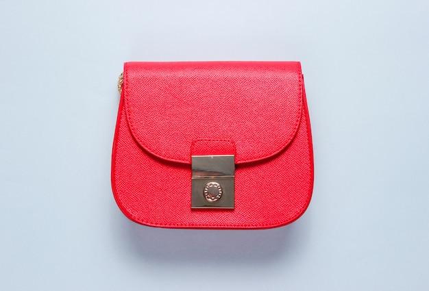 Czerwona skórzana mini torebka na szarej powierzchni