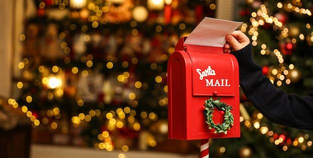 Czerwona skrzynka na listy do świętego mikołaja na tle bożego narodzenia