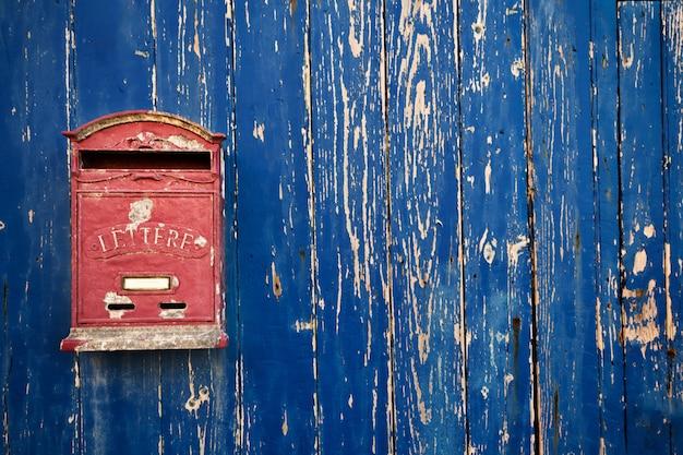 Czerwona skrzynka pocztowa na niebieskich drewnianych drzwiach z bliska