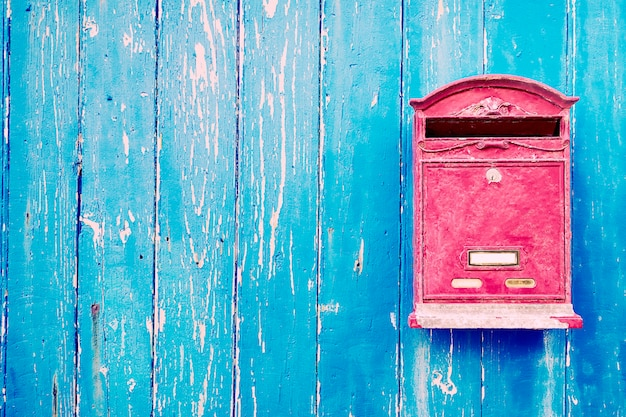 Czerwona skrzynka pocztowa na niebieskich drewnianych drzwiach