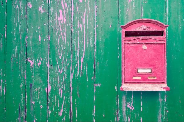 Czerwona skrzynka pocztowa na zielonych drewnianych drzwiach