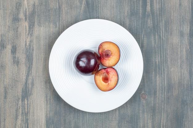 Czerwona śliwka wiśniowa samodzielnie na białym talerzu