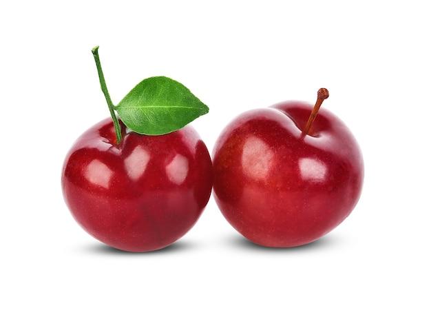 Czerwona śliwka wiśniowa z zielonymi liśćmi na białym tle