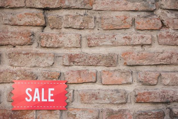 Czerwona sprzedaży pastylka na ściana z cegieł
