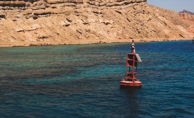 Czerwona stalowa boja nawigacyjna pływająca w błękitnej wodzie morskiej