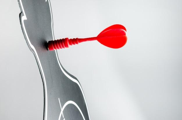 Czerwona strzałka w rzutki w kształcie profilu na szarym tle