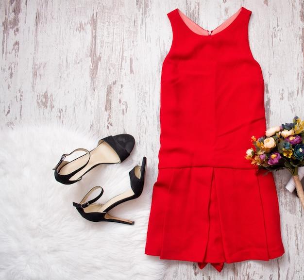 Czerwona sukienka, czarne buty i bukiet. sztuczne futro na podłoże drewniane, koncepcja modna, widok z góry