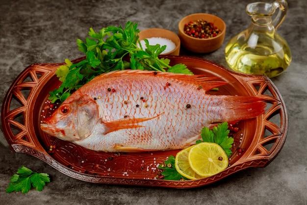 Czerwona surowa ryba tilapia z ziołami, przyprawami i oliwą z oliwek.