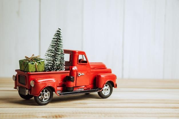 Czerwona świąteczna ciężarówka z sosną i prezentem. wesołych świąt i szczęśliwego nowego roku koncepcja.