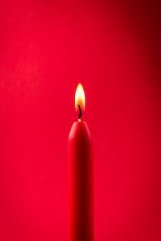Czerwona świeca pali się na czerwonym tle.