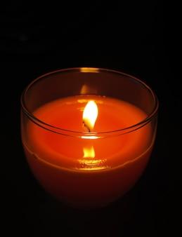 Czerwona świeca w przezroczystym szklanym świeczniku płonąca w ciemności