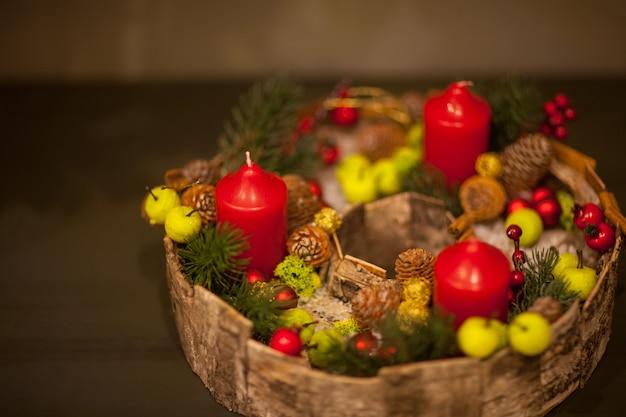 Czerwona świeczka bożonarodzeniowa w koszu z jagodami i szyszkami jodłowymi z zielonymi jabłkami