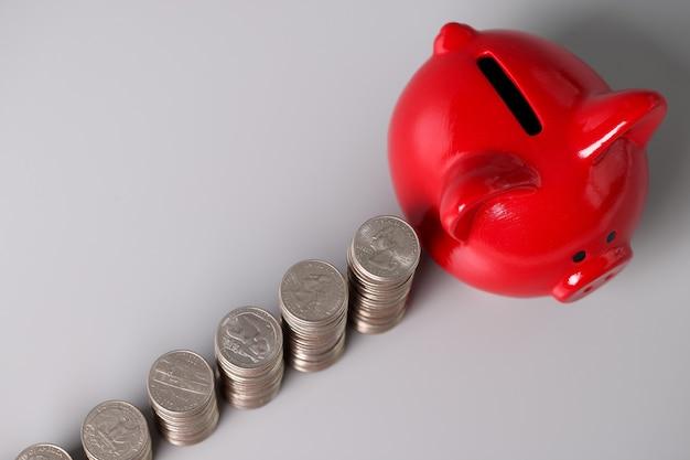 Czerwona świnia skarbonka i stosy monet na stole. koncepcja akumulacji akumulacyjnej