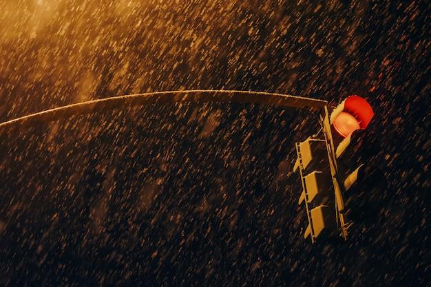 Czerwona sygnalizacja świetlna w ciemnym czasie z bliska. sygnalizacja świetlna przy silnych opadach śniegu. ogromne płatki śniegu nad drogą. zatrzymaj sygnał w nocy. przepisy ruchu drogowego. brak korków.