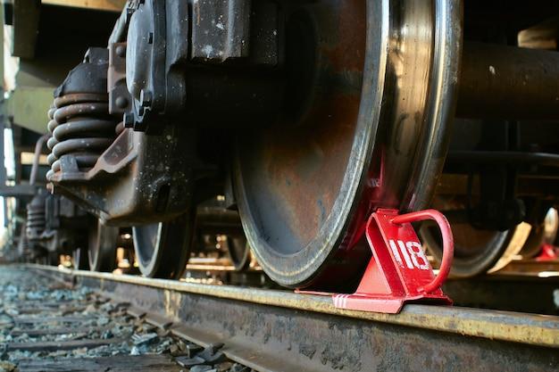 Czerwona szczęka hamulcowa kolejowa zamocowana pod taborem.
