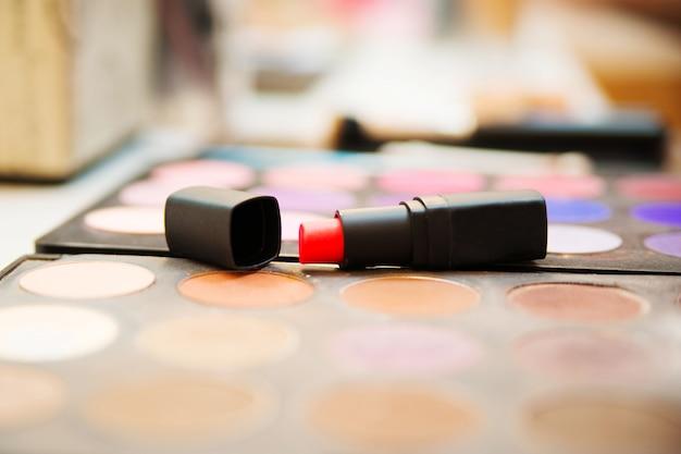 Czerwona szminka leży na palecie kolorowych cieni do powiek