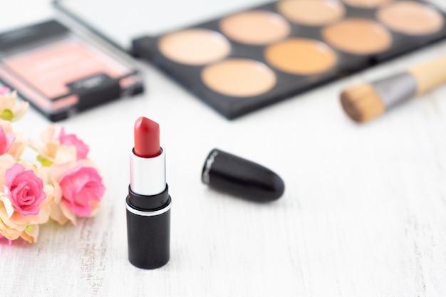 Czerwona szminka z zestawem kosmetyków dekoracyjnych.