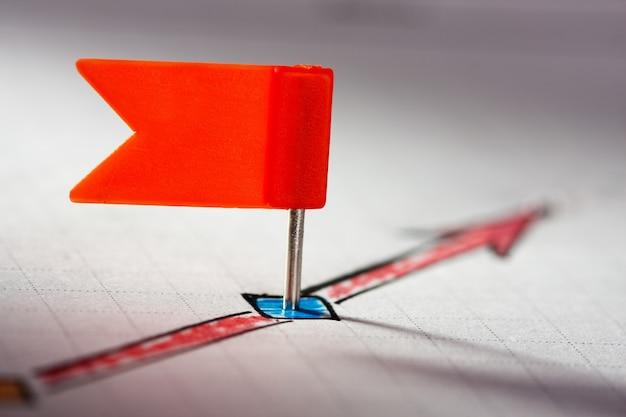 Czerwona szpilka na naszkicowanych czerwonych strzałkach