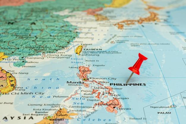 Czerwona szpilka umieszczona selektywnie na mapie filipin. - koncepcja ekonomiczna i biznesowa.