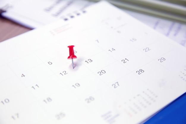 Czerwona szpilka w kalendarzu dla biznesu i spotkania planner.