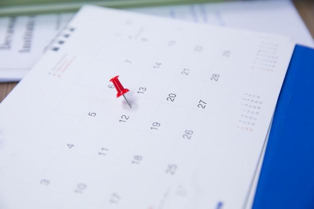 Czerwona szpilka z kalendarzem do planowania imprez.