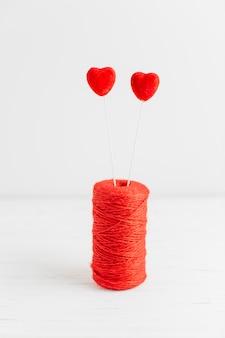 Czerwona szpula do szycia z dwoma sercami na patykach