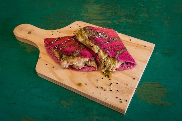 Czerwona tapioka z nadzieniem z kurczaka - na drewnianym stole