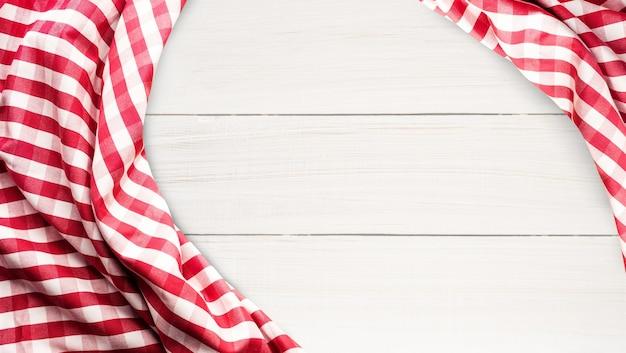 Czerwona tkanina w kratkę na tle biały stół z drewna