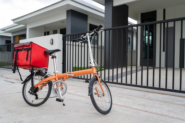 Czerwona torba umieszczona na rowerze przygotowana do dostarczania przesyłek do klientów