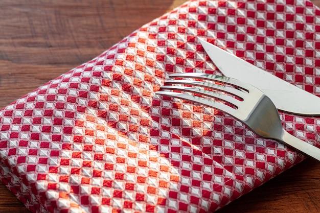 Czerwona w kratkę pielucha lub tablecloth na drewnianym stole, kopii przestrzeń