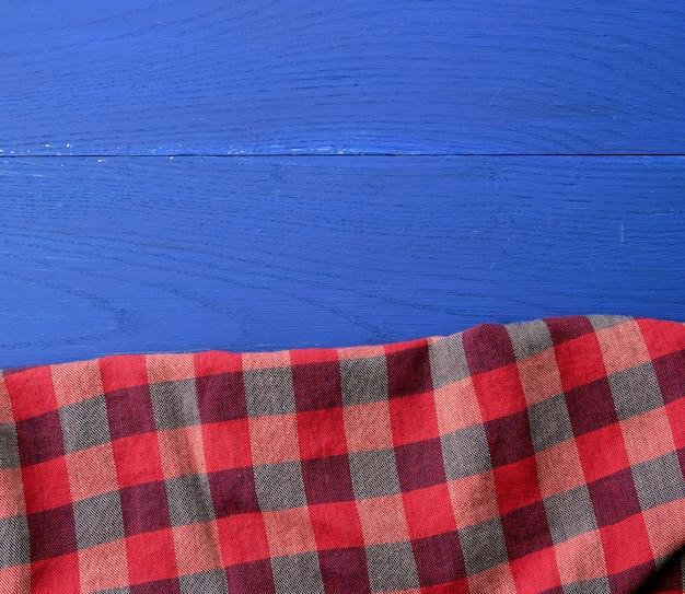 Czerwona w kratkę tkanina na błękitnym drewnianym tle